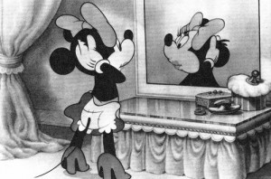 Early Disney still of Minnie Mouse dolling herself up. Patched clothes, loose shoes, black skin.