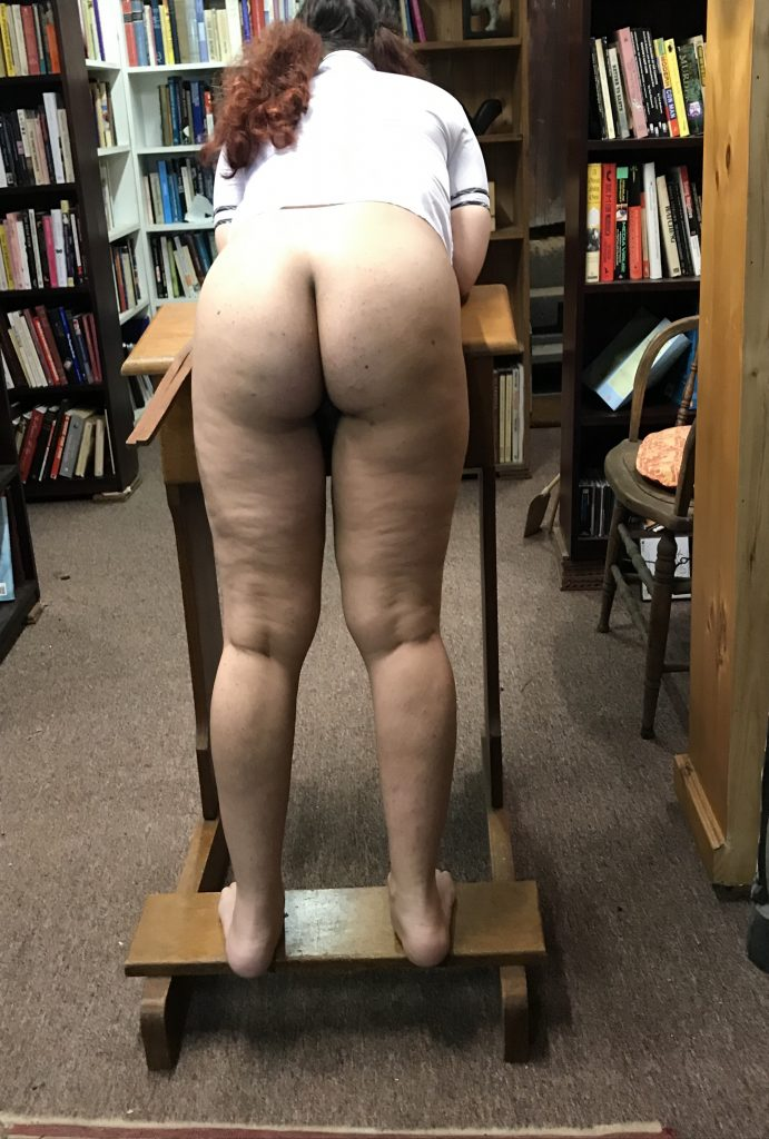 She bends over, naked, for the tawse